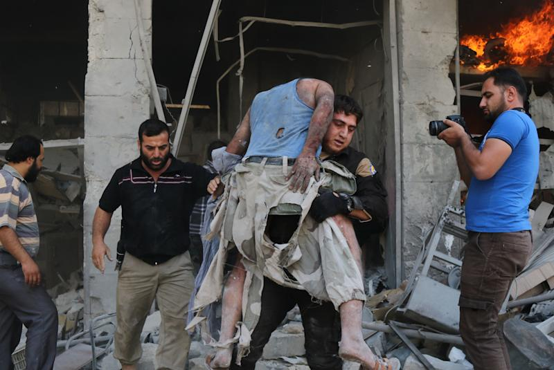 A member of the Syrian Civil Defense, also known as White Helmets, carries a victim following the airstrike at the Maaret al-Numan market. (MOHAMED AL-BAKOUR via Getty Images)
