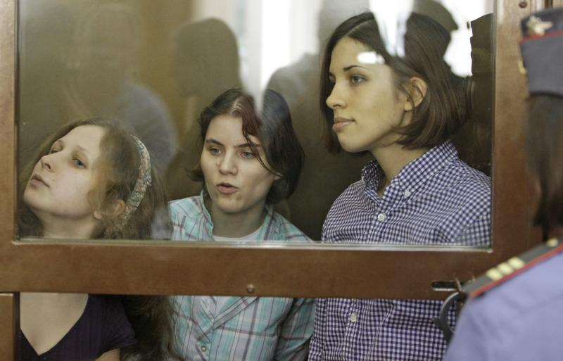"From left, Yekaterina Samutsevich, Maria Alekhina, Nadezhda Tolokonnikova, members of feminist punk group Pussy Riot sit behind bars at a court room in Moscow, Russia, Russia, Monday, July 30, 2012.Three members of the band are facing trial for performing a ""punk prayer"" against Vladimir Putin from a pulpit of Moscow's main cathedral before Russia's presidential election in March, in which he won a third term. (AP Photo/Mikhail Metzel)"