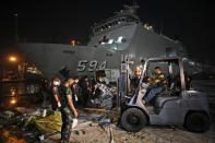 Workers remove parts of the wreckage of Sriwijaya Air flight SJ-182 that crashed into the Java Sea on Jan. 9, to be loaded onto a truck and transported for further investigation, at Tanjung Priok Port in Jakarta, Indonesia, Thursday, Jan. 21, 2021. Indonesian authorities on Thursday ended the search for the wreckage of the plane that nose-dived into the sea, killing all of its passengers on board. (AP Photo/Dita Alangkara)