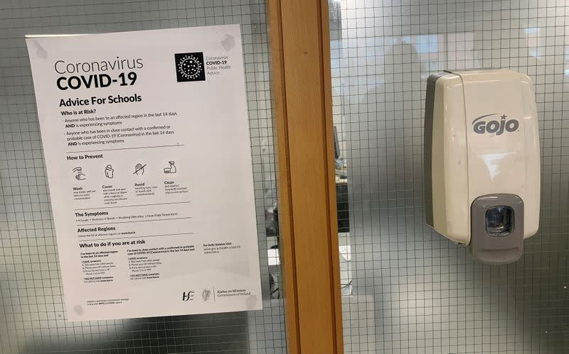 A coronavirus advice notice is seen next to an anti-bacterial gel dispenser in a college in Dublin, Ireland