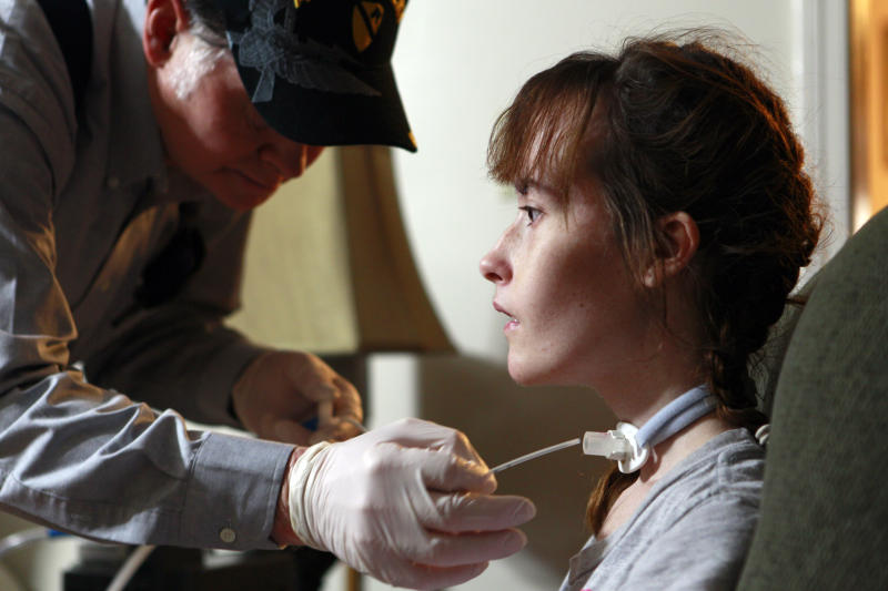In this Saturday, Nov. 20, 2010 photo, Sabrina Parker's grandfather, Noland Parker, cleans her trachea tube at his home in Jacksonville, N.C. Sabrina passed away on Nov. 30, 2010 from ALS, also known as Lou Gehrig's Disease, which also killed her mother and grandmother. (AP Photo/Gerry Broome)