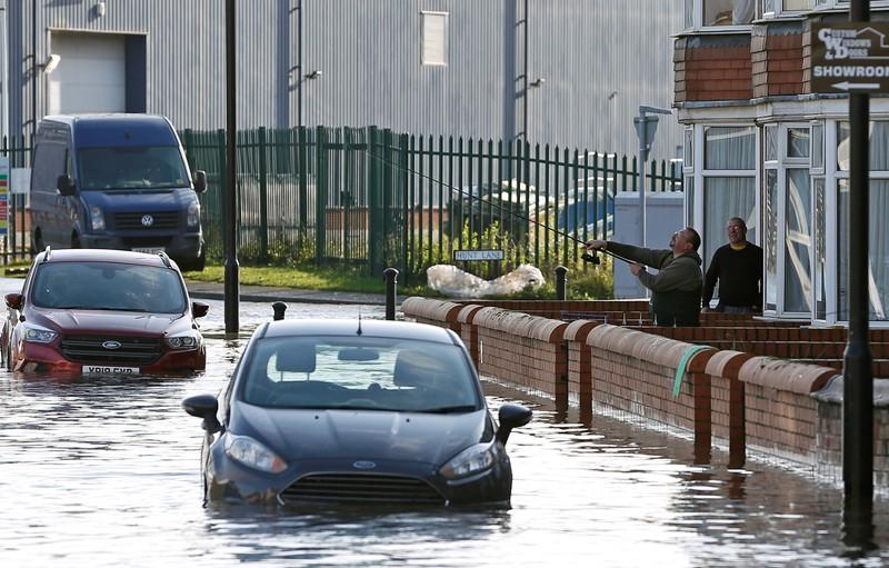 A man holds a fishing rod over a flooded street in Bentley, north of Doncaster