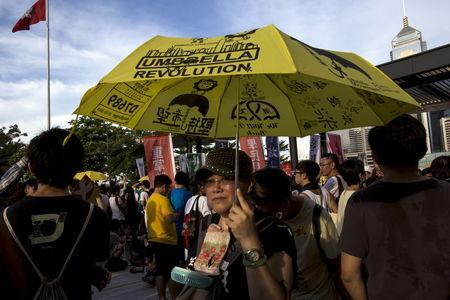 A pro-democracy protester holds a umbrella, the symbol of the Occupy Central movement, during a march to demand lawmakers reject a Beijing-vetted electoral reform package for the city's first direct chief executive election, near a Hong Kong flag (top L) outside the Legislative Council building in Hong Kong, China June 14, 2015. REUTERS/Tyrone Siu