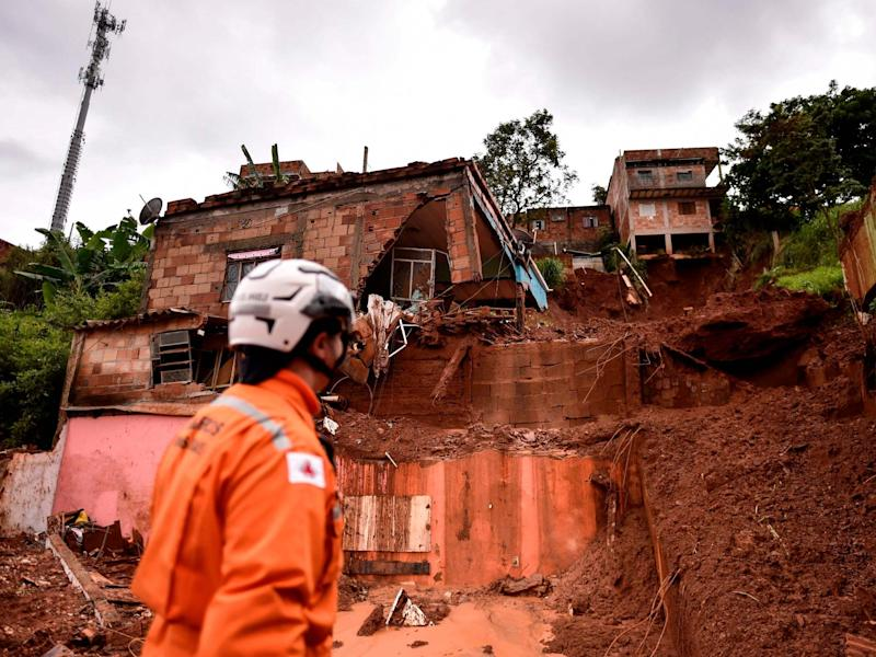 A firefighter looks at the site of a landslide in Belo Horizonte: AFP via Getty Images