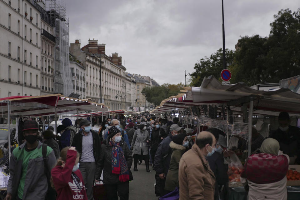 People wearing protective face masks as precaution against the conoravirus shop at an outdoor market in Paris, Friday, Oct. 30, 2020. France re-imposed a monthlong nationwide lockdown Friday aimed at slowing the spread of the virus, closing all non-essential business and forbidding people from going beyond one kilometer from their homes except to go to school or a few other essential reasons. (AP Photo/Thibault Camus)