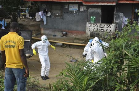 Medical staff wearing protective suits gather at a health facility near the Liberia-Sierra Leone border in western Liberia November 5, 2014. REUTERS/James Giahyue