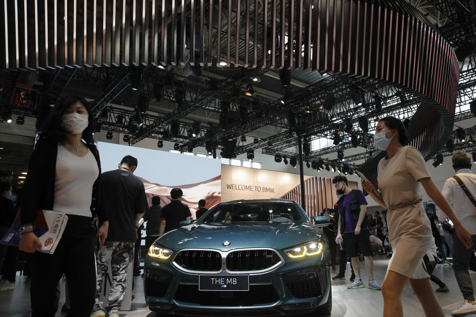 FILE - In this Sept. 27, 2020 file photo, visitors gather near a BMW M8 model on display at the Auto China 2020 show in Beijing, China. German automaker BMW said third-quarter net profit rose 17% to 1.81 billion euros ($2.22 billion) as regional auto markets recovered and highly profitable luxury models such as the 8 Series coupe and X7 large sport-utility vehicle helped fatten the bottom line. (AP Photo/Andy Wong, File)