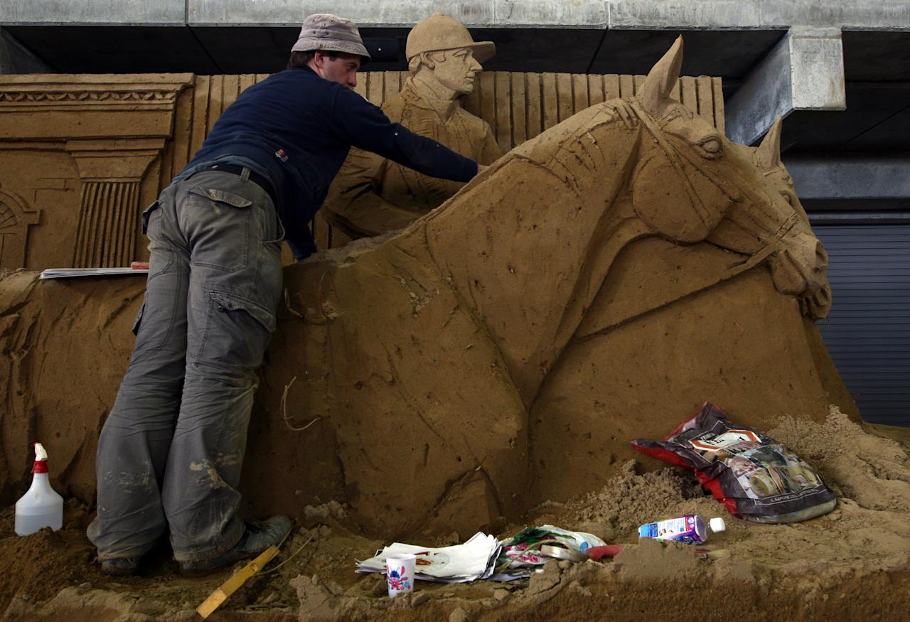 Alexey Shchitov of Russia finishes a sand replica titled 'Queen Elizabeth II with the Horse Wagon' at Sand Museum located in the Tottori Dune on April 1, 2012 in Tottori, Japan. (Photo by Buddhika Weerasinghe/Getty Images)