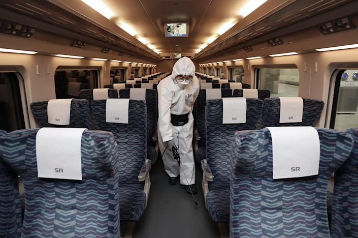 A worker wearing protective gears sprays disinfectant as a precaution on a train against the new coronavirus at Suseo Railway Station in Seoul, South Korea, Tuesday, Feb. 25, 2020. China and South Korea on Tuesday reported more cases of a new viral illness that has been concentrated in North Asia but is causing global worry as clusters grow in the Middle East and Europe. (Lee Ji-eun/Yonhap via AP)