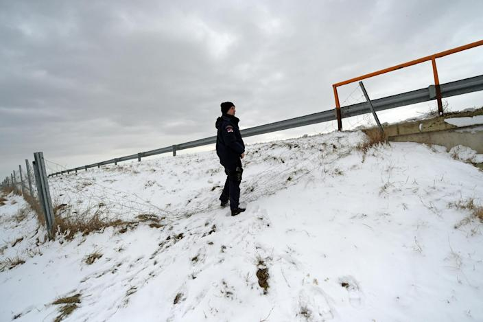 A Serbian border police officer checks a vandalised fence near the Hungarian border in the northern Serbian village of Backi Vinogradi on February 9, 2015 (AFP Photo/Andrej Isakovic)
