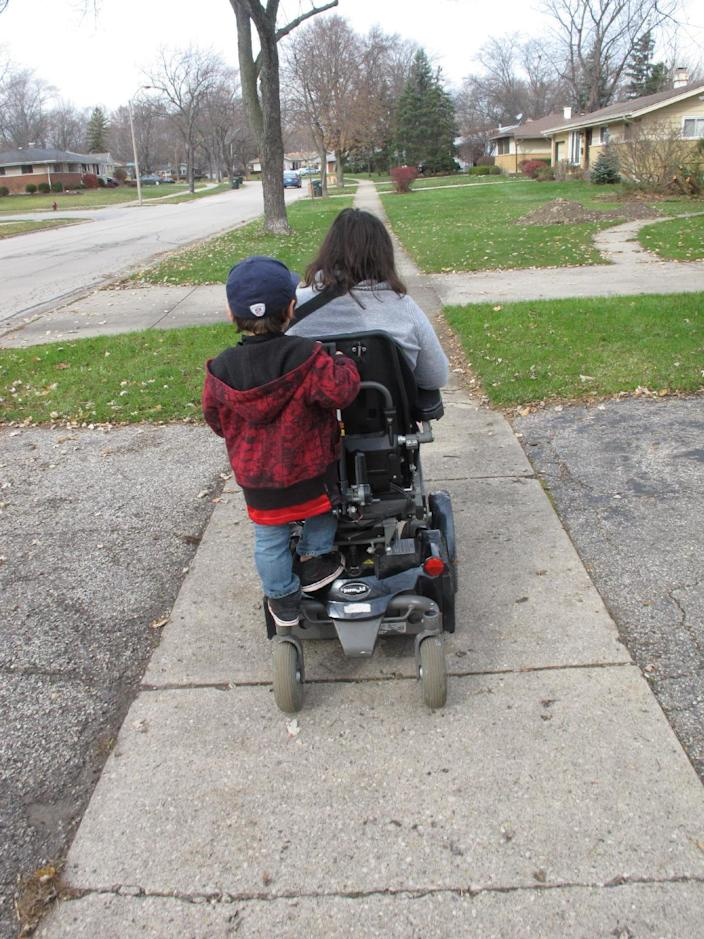 In this Monday, Nov. 19, 2012 photo, Noah Thomas, 8, rides on the motorized wheelchair of his mother, Jenn Thomas, on their way to a school book fair in Arlington Heights, Ill. Jenn Thomas was born with cerebral palsy. A report from the National Council on Disability found that 6.1 million children, about 10 percent of the overall U.S. population, have parents with some sort of disability. (AP Photo/Martha Irvine)