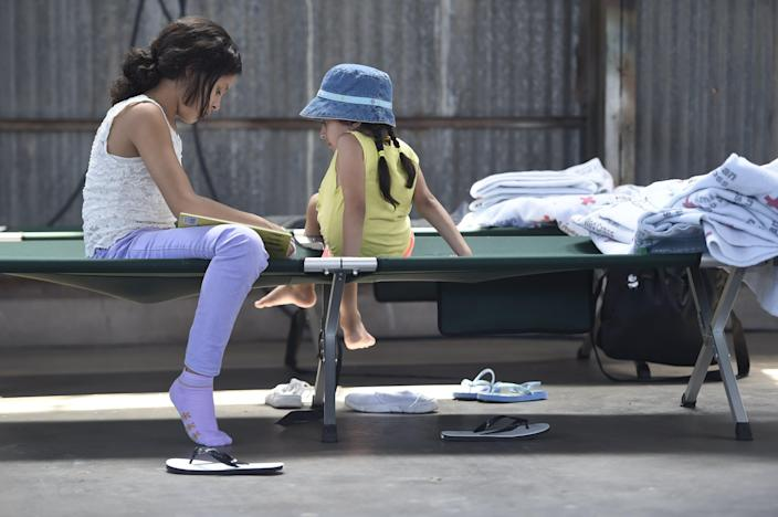 Two migrant children read on a cot in a migrant shelter June 28, 2019, in Deming, N.M.
