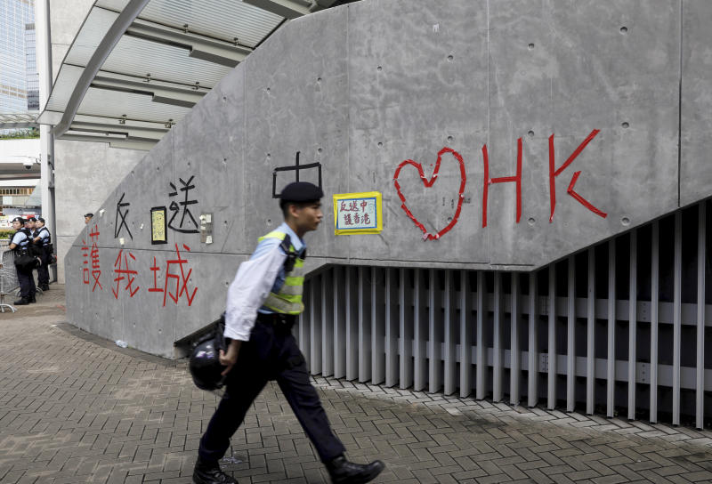 "A police officer passes by ""Love Hong Kong"" words formed with tape near the Legislative Council in Hong Kong on Friday, June 14, 2019. Calm appeared to have returned to Hong Kong after days of protests by students and human rights activists opposed to a bill that would allow suspects to be tried in mainland Chinese courts. (AP Photo/Vincent Yu)"