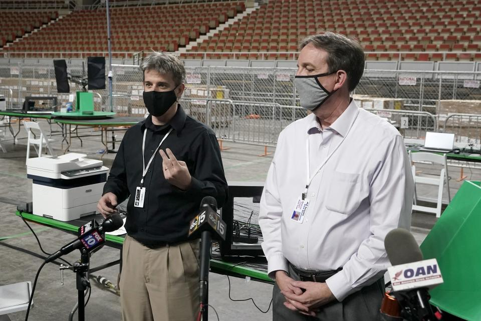 Cyber Ninjas owner Doug Logan, left, a Florida-based consultancy, and former Arizona Secretary of State Ken Bennett, right, talk about overseeing a 2020 election ballot audit at the Arizona Veterans Memorial Coliseum, during a news conference Thursday, April 22, 2021, in Phoenix. The equipment used in the November election won by President Joe Biden and the 2.1 million ballots were moved to the site Thursday so Republicans in the state Senate who have expressed uncertainty that Biden's victory was legitimate can recount them and audit the results. (AP Photo/Ross D. Franklin)