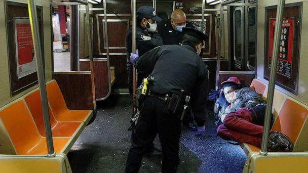 PHOTO: NYPD and MTA officers wake up a sleeping passenger before directing him to exit the 207th Street A-train station, April 30, 2020, in New York City. (John Minchillo/AP)