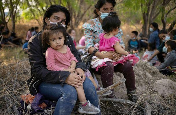 PHOTO: Asylum seeking migrant mothers from Honduras hold their children after crossing the Rio Grande river into the United States from Mexico on rafts in Penitas, Texas, March 26, 2021.  (Adrees Latif/Reuters)