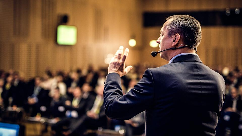 Rear view of a businessman entrepreneur giving a lecture to a sold-out crowd in a lecture hall.