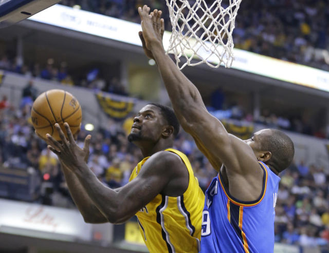 Indiana Pacers guard Lance Stephenson, left, shoots under Oklahoma City Thunder forward Serge Ibaka in the second half of an NBA basketball game in Indianapolis, Sunday, April 13, 2014. The Pacers defeated the Thunder 102-97. (AP Photo/Michael Conroy)