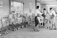 <p>A group of young men working as bag boys load up several grocery carts with pre-ordered goods. As it turns out, curbside pickup isn't so new after all. </p>