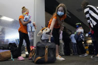 Hawaii residents Ella Sidlow, center, pets her dog Cookie between her sister Sienna, left, and mother Gina, right, as they wait to return home on a United Airlines flight to Hawaii at San Francisco International Airport in San Francisco, Thursday, Oct. 15, 2020. Coronavirus weary residents and struggling business owners in Hawaii will be watching closely as tourists begin to return to the islands on Thursday without having to self-quarantine upon arrival. (AP Photo/Jeff Chiu)