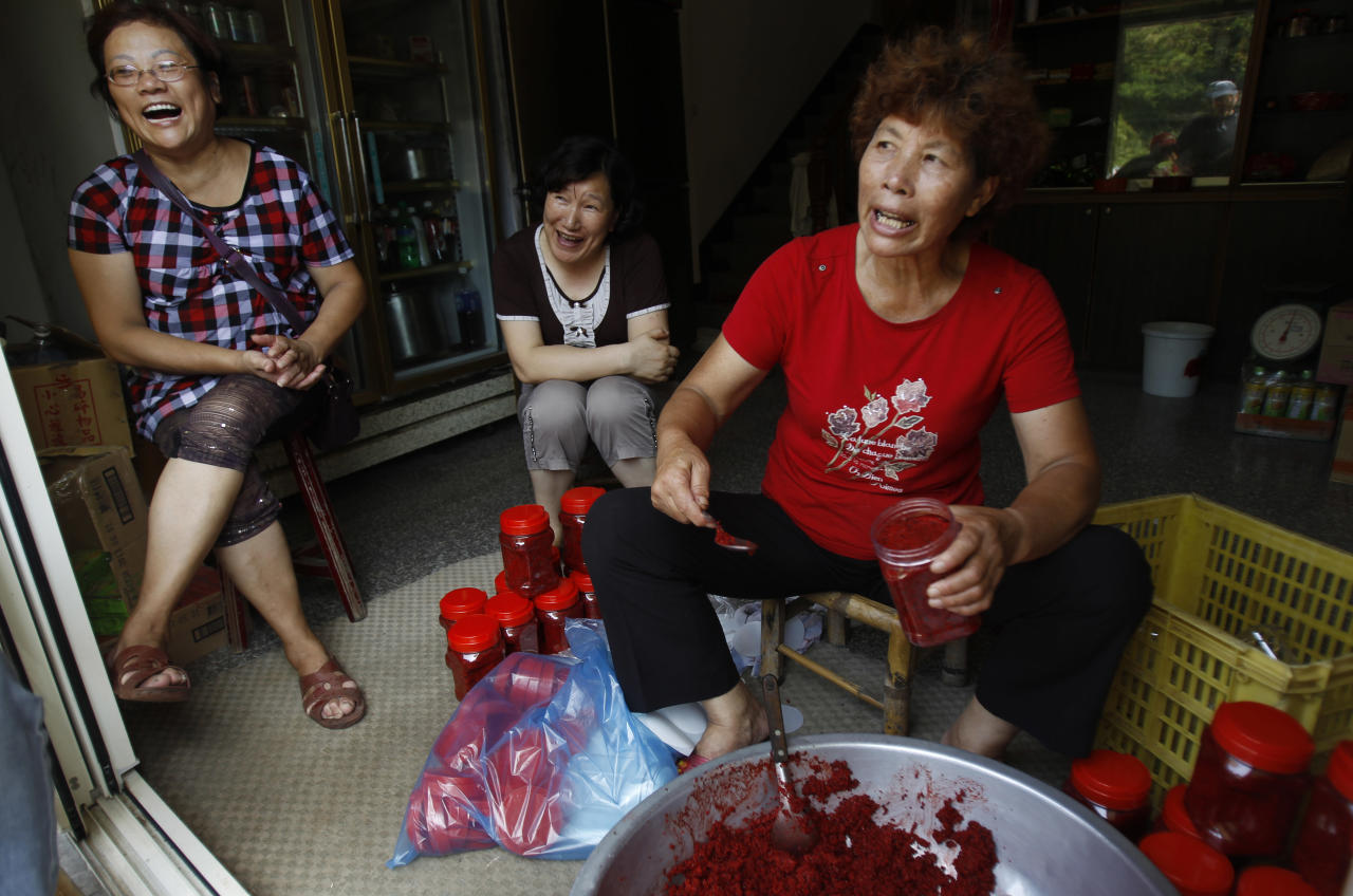 In this Aug. 21, 2012 photo, Lin, in red, sits with friends as they fill jars of red sorgum, a local delicacy, and talk about why they voted for the proposed casino to be built on Beigan in the Matsu island group, off northern Taiwan. In early July some 3,000 Matsu residents voted 57 to 43 to permit casino gambling. Their votes were clearly influenced by the promises of not only a casino, but also a tourist resort, expanded airport, roadway infrastructure, a university, and perhaps most alluring of all, a monthly payment of 80,000 New Taiwan dollars ($2,666) for every resident. (AP Photo/Wally Santana)