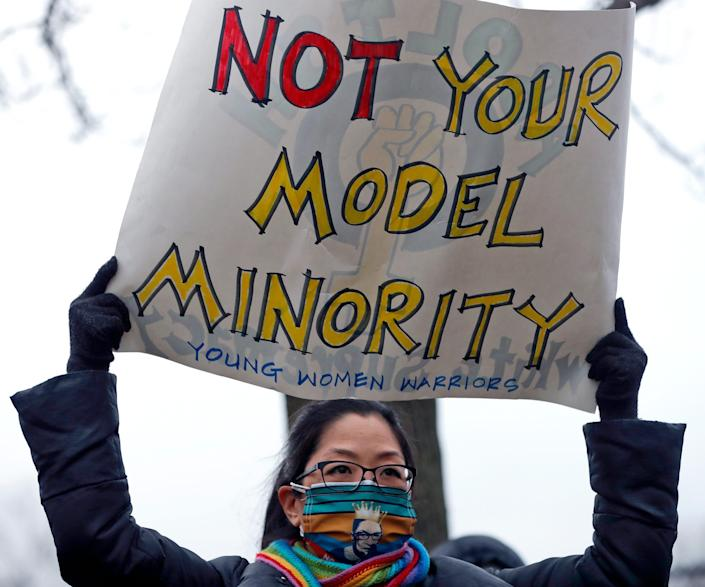 A woman wearing a Justice Ruth Bader Ginsburg face mask holds a sign during a vigil and rally against Asian hate crimes, Friday, March 26, 2021, at Chicago's Horner Park. The event is organized by local Chicago organizations led by Asian Americans and Pacific Islanders. (AP Photo/Shafkat Anowar) ORG XMIT: ILSA105