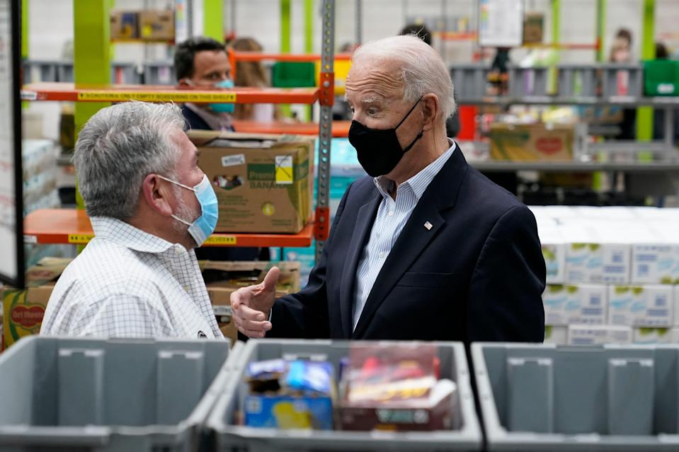President Joe Biden talks with a volunteer at the Houston Food Bank, Friday, Feb. 26, 2021, in Houston.