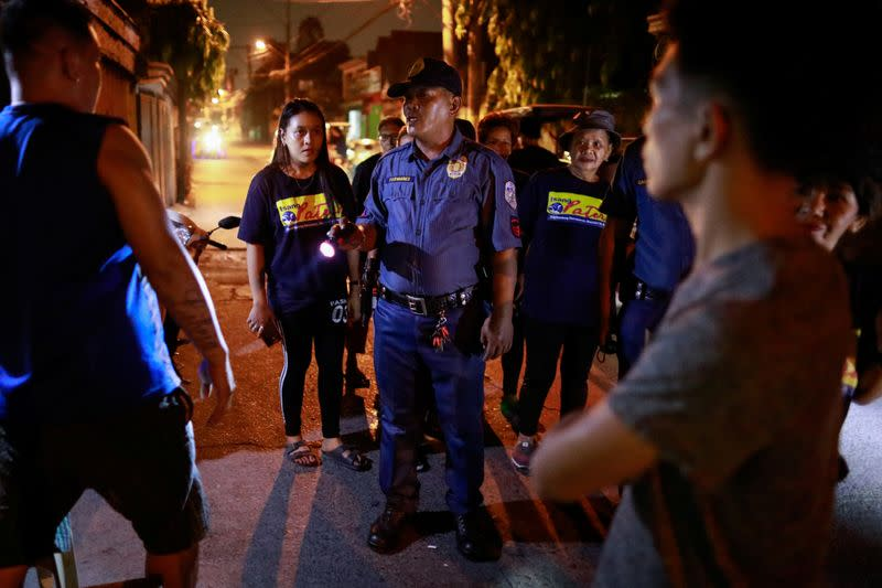 A policeman reprimands men for drinking in public, while accompanying a volunteer group of women patrollers on the streets of Pateros