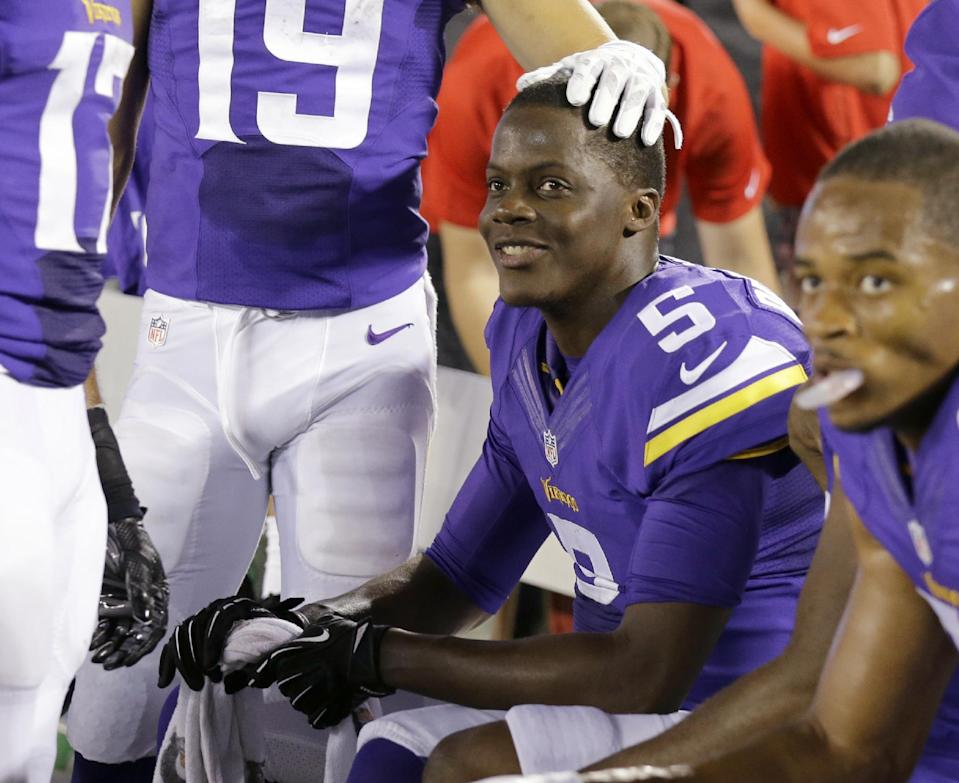 Minnesota Vikings quarterback Teddy Bridgewater (5) is congratulated by a teammate as he sits on the bench during the final seconds of an NFL preseason football game against the Arizona Cardinals, Saturday, Aug. 16, 2014, in Minneapolis. The Vikings won 30-28. (AP Photo/Ann Heisenfelt)