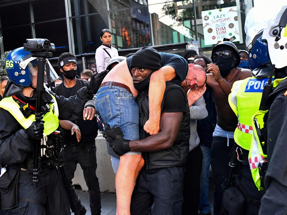 Protester Patrick Hutchinson carries an injured counter-protester to safety, near Waterloo station during a Black Lives Matter protest following the death of George Floyd in Minneapolis police custody, in London, Britain, June 13, 2020.
