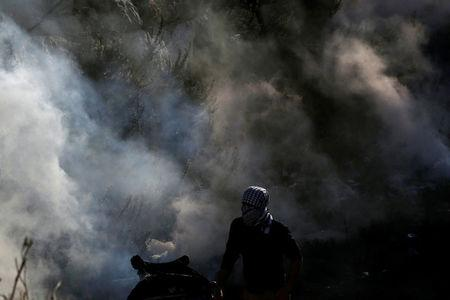A Palestinian protester looks on as tear gas and smoke are seen during clashes with Israeli troops at a protest against U.S. President Donald Trump's decision to recognize Jerusalem as the capital of Israel, near the Jewish settlement of Beit El, near the West Bank city of Ramallah December 7, 2017. REUTERS/Mohamad Torokman