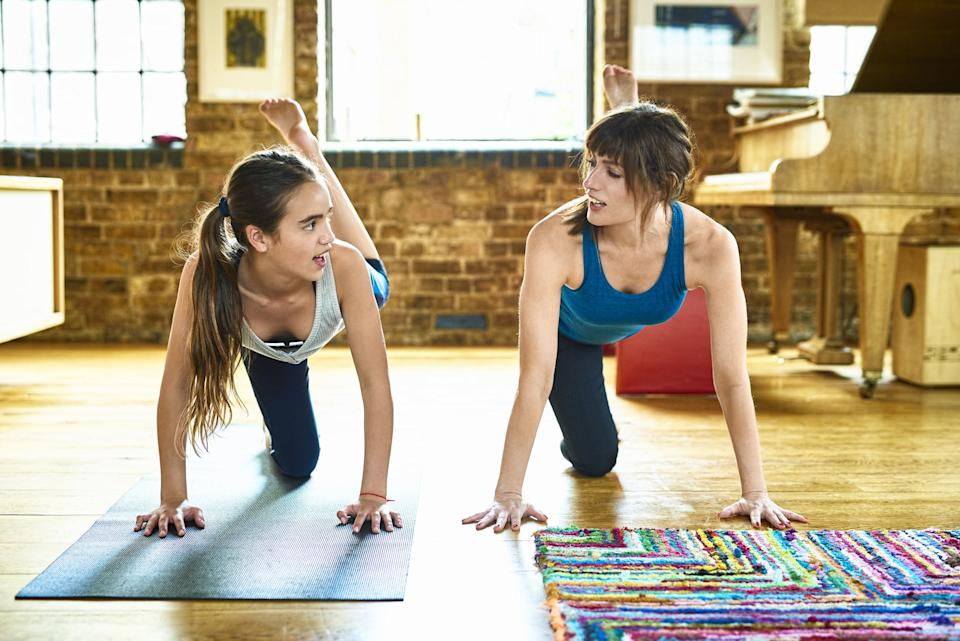Mother and daughter practicing yoga in livingroom