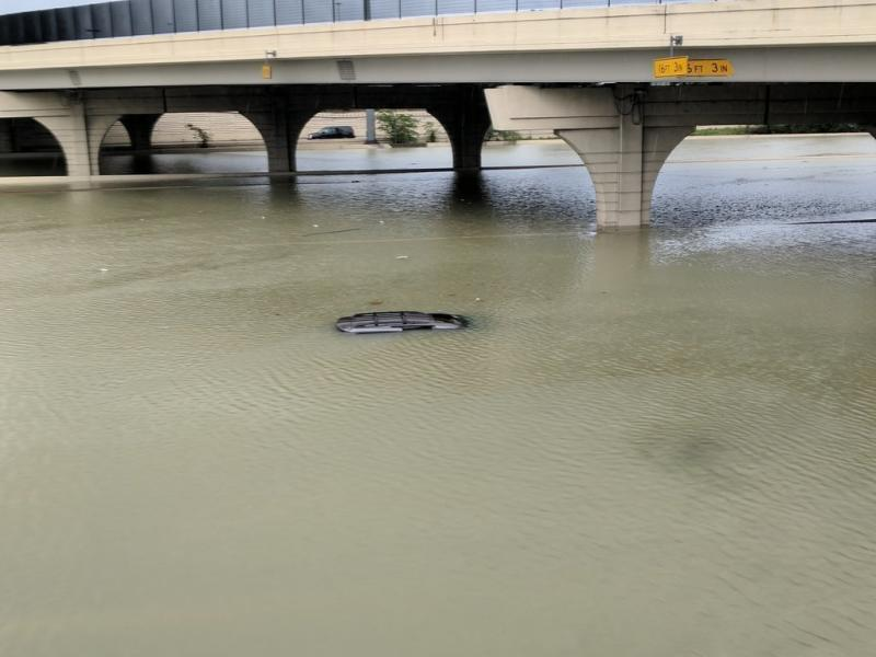 The roof of a submerged car is just barely visible beneath a bridge in Houston on Sunday. (Roque Planas/HuffPost)