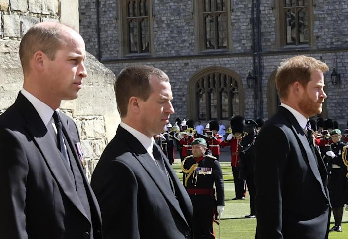 Prince William, Peter Phillips and Prince Harry walk past military members on the grounds of Windsor Castle.