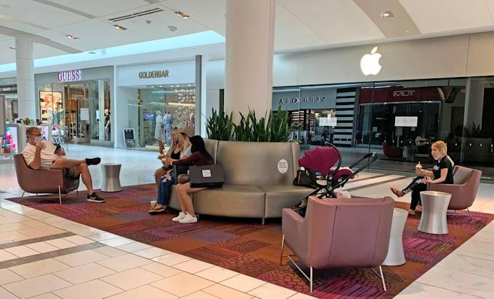 Shoppers take a break at Dadeland Mall. Some guests removed their masks to eat or drink takeout items they'd bought elsewhere in the mall.