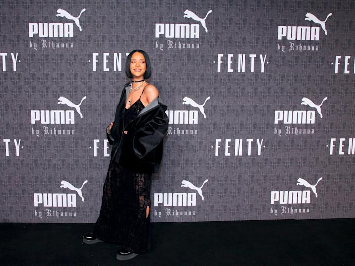 Rihanna stands in front of Puma and Fenty wall at fashion show