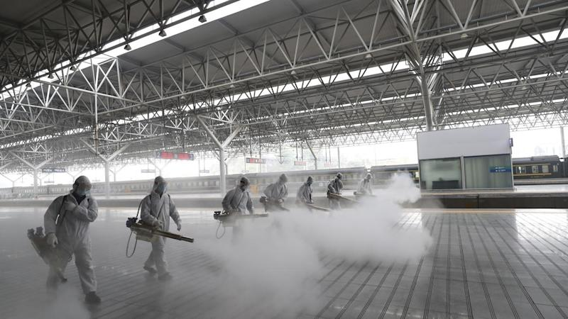 Frefighters disinfect a railway platform in Yichang in Hubei, which has had restrictions lifted