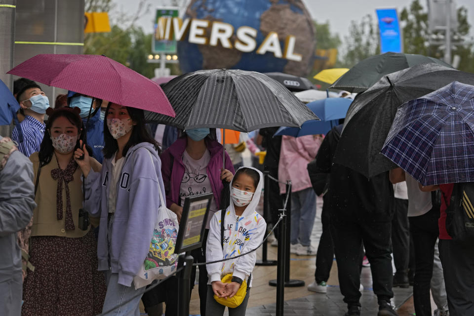 Visitors line-up to enter a merchandise store at the Universal Studios Beijing in Beijing, Monday, Sept. 20, 2021. Thousands of people brave the rain visit to the newest location of the global brand of theme parks which officially opens on Monday. (AP Photo/Andy Wong)