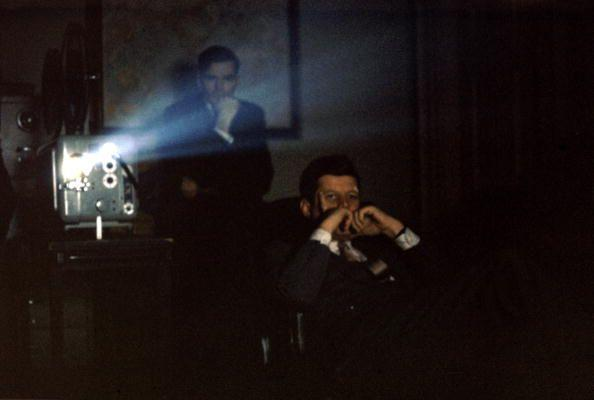 <p>President Kennedy views a film in the office of Press Secretary Pierre Salinger.</p>