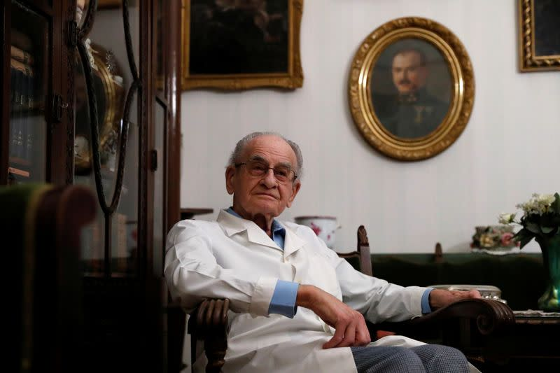 Kormendi, 97-year-old doctor, poses for a picture in his doctor's office at his home in Budapest