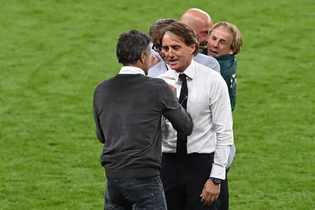 Roberto Mancini, right, greets Spain manager Luis Enrique after the game