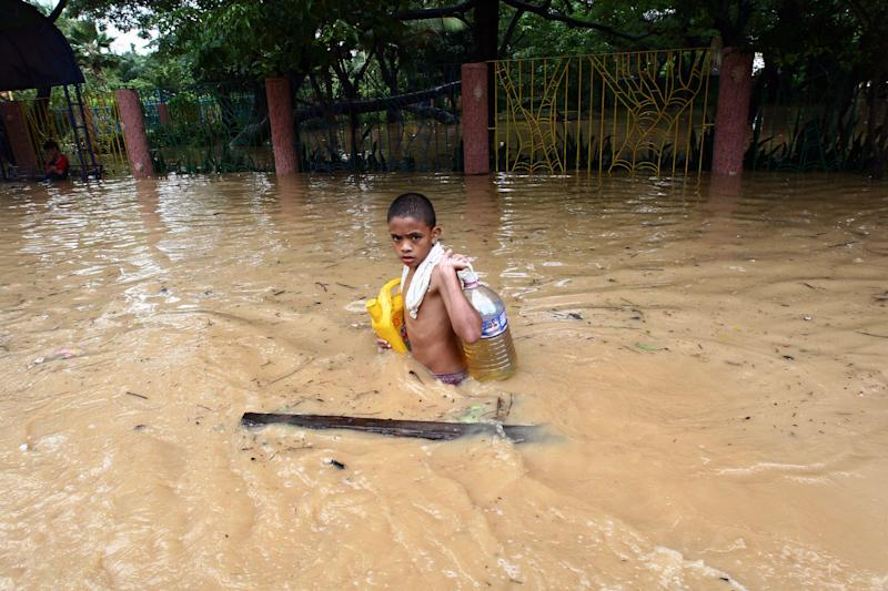 A boy carries supplies through waist-high floodwater in Pasig City in Manila, the capital. On Sept. 30,2009, in the Philippines, over half a million people are displaced by flooding caused by Tropical Storm Ketsana, which struck on Sept. 26. The storm dumped over a month's worth of rain on the island of Luzon in only 12 hours. The flooding has affected some 1.8 million people, and the death toll has climbed to 246.