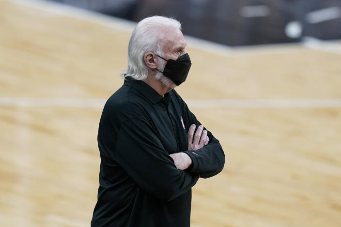 Gregg Popovich wears a face mask and has his arms crossed on the sideline of a game.