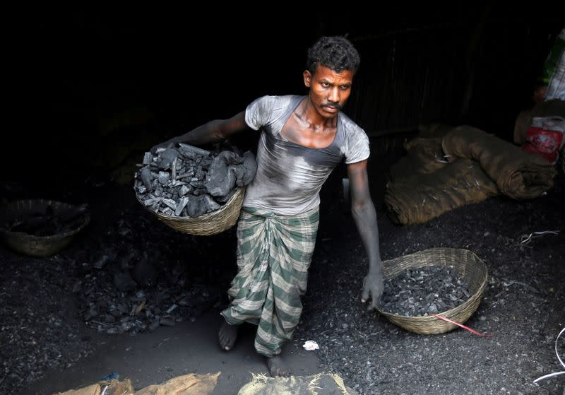 FILE PHOTO: A worker carries coal in a basket in a industrial area in Mumbai
