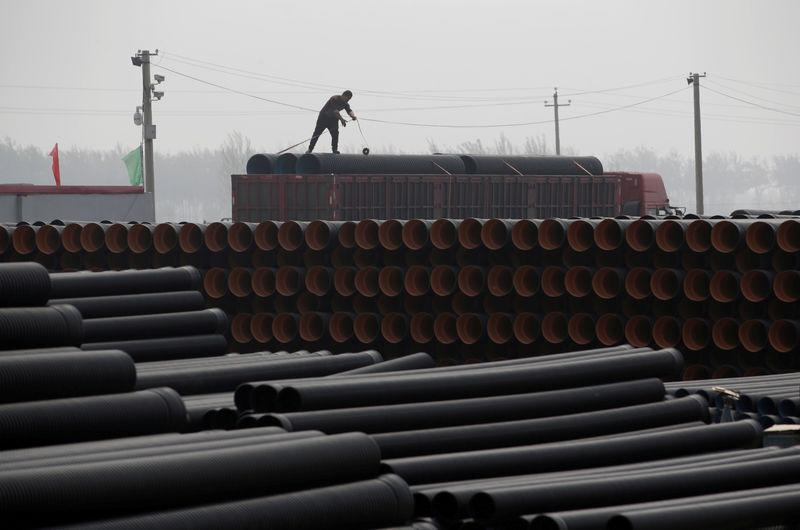 FILE PHOTO: A worker packs pipelines onto a truck at a local plastic pipe factory in Donghegang village on the outskirts of Xiongxian county