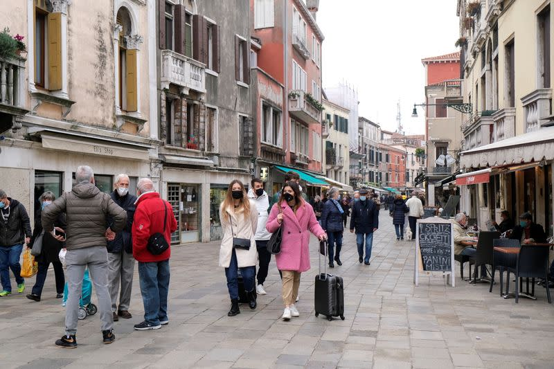 People wearing masks walk on a street, as the number of people infected by the coronavirus disease (COVID-19) continues to rise, in Venice