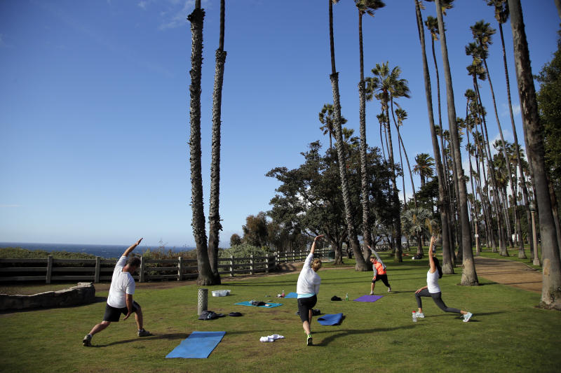 In this photo taken Tuesday, Dec. 18, 2012, a group of people stretch during their fitness class at Palisades Park in Santa Monica, Calif. City officials say the park is being overrun by people operating everything from boot camps to yoga classes to massage therapy sessions. Officials are considering making such operators cut the city in on 15 percent of their profits and pay an annual $100 permit fee for the right to do business in the park. (AP Photo/Jae C. Hong)