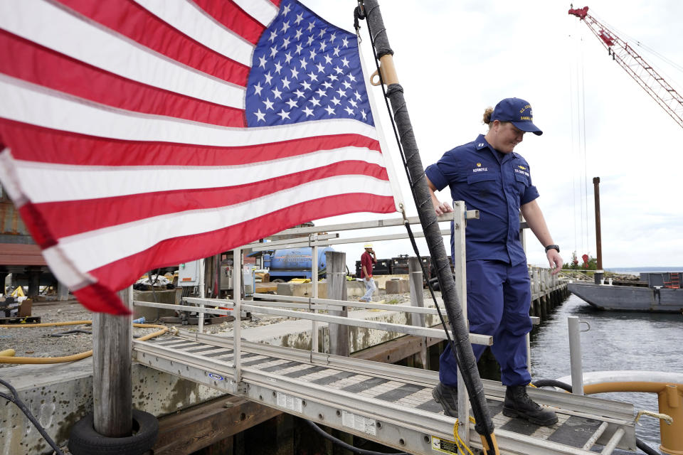 """U.S. Coast Guard Lt. Kelli Normoyle, Commanding Officer of the Coast Guard Cutter Sanibel steps aboard the vessel, Thursday, Sept. 16, 2021, at a shipyard, in North Kingstown, R.I. Normoyle was one of two cadets who formally started the process to create the CGA Spectrum Diversity Council just a few months after the law known as """"don't ask, don't tell"""" was repealed on Sept. 20, 2011. (AP Photo/Steven Senne)"""