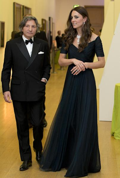 Kate Duchess of Cambridge walks with a guest a fund raising gala at the National Portrait Gallery in London, Tuesday, Feb. 11, 2014. The Duchess is wearing a dress by British designer Jenny Packham and a necklace on loan from Queen Elizabeth II that was given to the Queen as a gift for her wedding in 1947. (AP Photo/Alastair Grant, Pool)