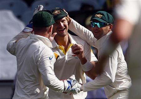 Australia's Shane Watson (C) is congratulated by teammates Brad Haddin (L) and captain Michael Clarke after he caught out England's Ben Stokes for 14 runs, during the first day of the fourth Ashes cricket test at the Melbourne cricket ground December 26, 2013. REUTERS/David Gray